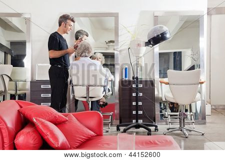 Male hairstylist straightening client's hair at beauty salon