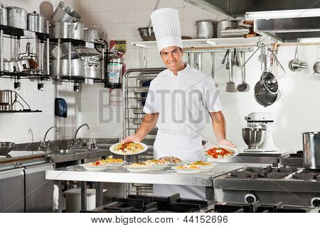 Portrait of confident male chef presenting pasta dishes at commercial kitchen counter
