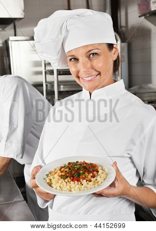 Portrait of female chef showing pasta dish with colleague in background
