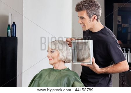 Mature male hairstylist showing finished haircut to senior female client at beauty parlor