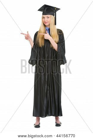 Full Length Portrait Of Young Woman In Graduation Gown Pointing On Copy Space