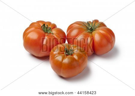 Organic Coeur de Boeuf tomatoes on white background
