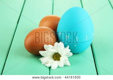 Blue egg timer and eggs, on color  wooden background