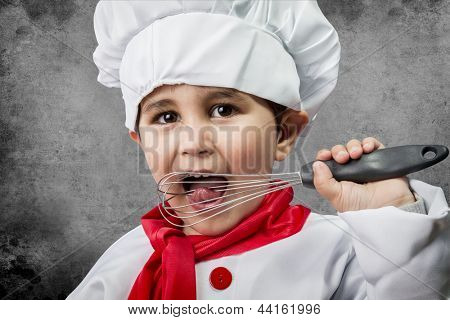 A little boy cook in uniform over vintage  background