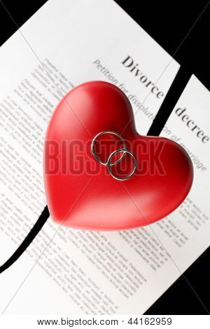 red heart with torn Divorce decree document, on black background close-up