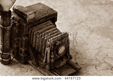 Background image of miniature vintage accordion style camera (model made from resin) on marbled tile.  Macro image in sepia tones with shallow dof and copy space.