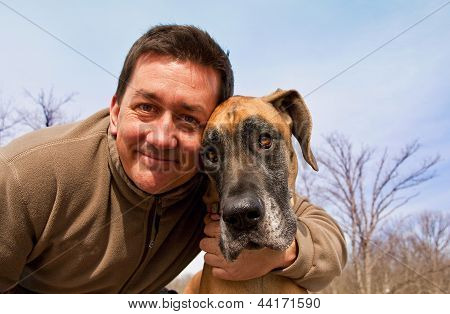 handsome man with arm around dog