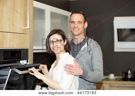 Happy Caucasian Couple In Front Ov The Oven