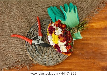 Secateurs with flowers on sackcloth on wooden background