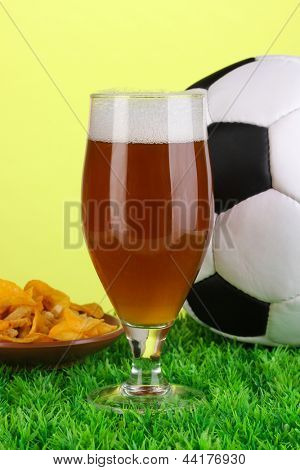 Glass of beer with soccer ball on grass on green background
