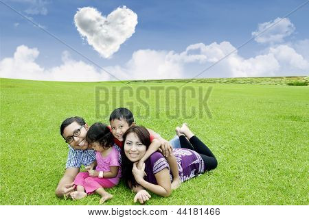 Happy Family Laying On The Grass