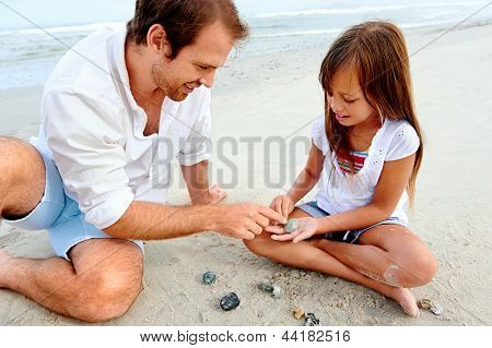 Father and daughter day at the beach collecting shells together having fun and smiling