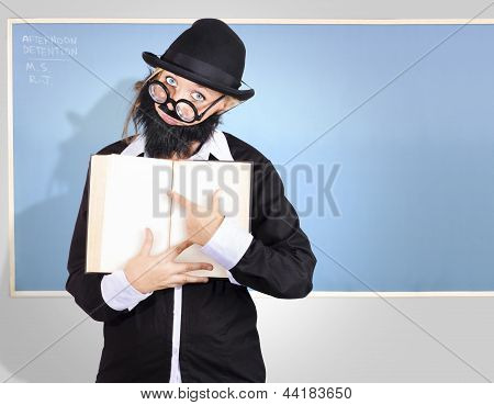 School Teacher In Classroom Pointing To Empty Book
