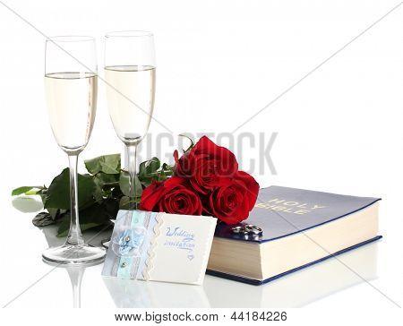 Anéis de casamento na Bíblia com rosas e copos de champanhe isolado no branco