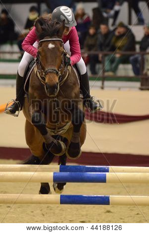 KAPOSVAR, HUNGARY - MARCH 24: Rebeka Marko jumps with her horse (Game Boy 4) on the Masters Tournament International Jumping Competition, March 24, 2013 in Kaposvar, Hungary