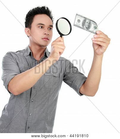 Man Looking Dollar Bill Through A Magnifying Glass