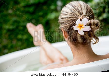 Beautiful woman relaxing at home and taking a bath
