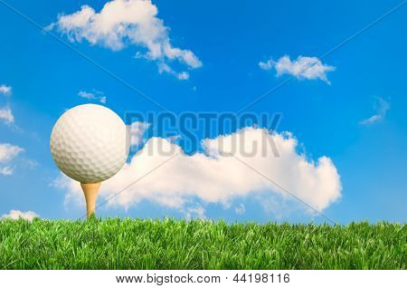 Golf ball on tee with blue sky background