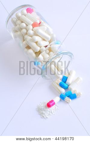 Multi colored capsules spilling from a bottle