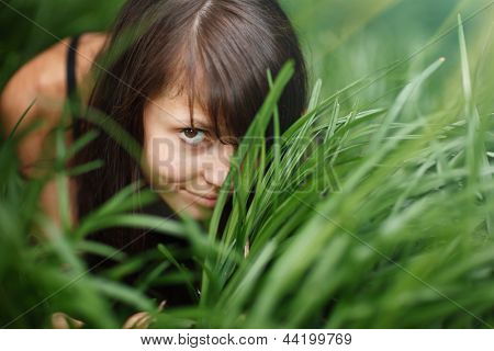 Portrait of beautiful girl hiding in green grass.