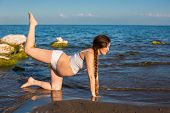 stock photo of pregnancy exercises  - Pregnant woman in sports bra doing exercise in relaxation on yoga pose on sea - JPG
