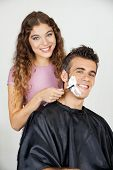 Portrait of happy man getting a shave from female barber at salon