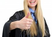 Closeup On Young Woman In Graduation Gown Showing Thumbs Up