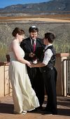stock photo of rabbi  - Rabbi blessing lesbian marriage ceremony in desert - JPG