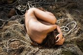 foto of nu  - Young naked woman and a fishing net on nature background - JPG
