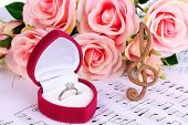 Treble clef, roses and box holding wedding ring on musical background