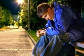 stock photo of banquette  - teenager sitting in the night park alley and looking on the watch - JPG