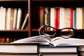 image of hardcover book  - Eyeglasses lying on the opened book and many other books on background - JPG