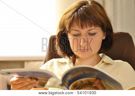 Young Woman Relaxing Reading A Magazine