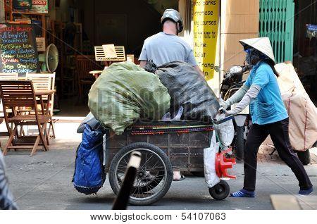 Unidentified street vendor carrying goods in Hanoi, Vietnam