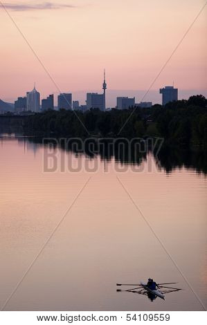 Rowing guys at dusk in the Danube River with urban skyline of Vienna