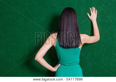 brunete lady against green wall from back