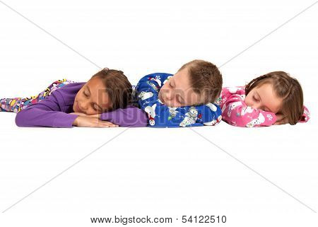Three Kids Laying Down Asleep In Winter Pajamas