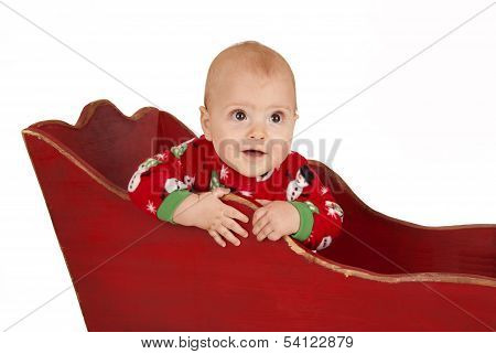 Toddler Boy In Red Christmas Pajamas In A Red Sleigh