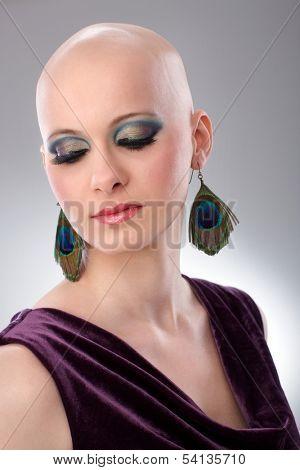 Studio portrait of hairless woman wearing elegant claret velvet dress.