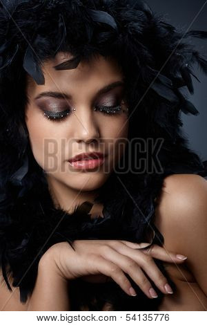 Beauty posing with black feather boa, extravagant eye makeup.