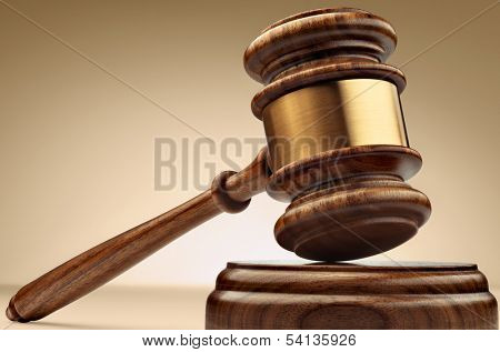 A wooden judge gavel and soundboard on brown background in perspective