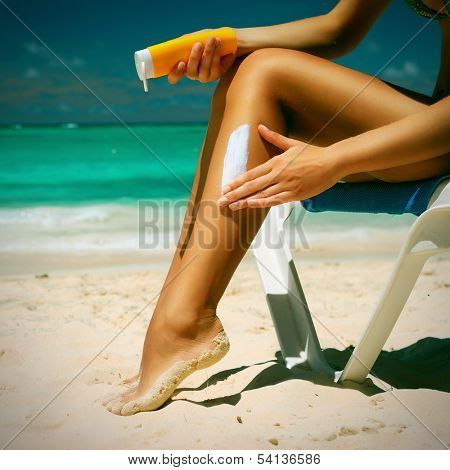 Tan woman applying sun protection lotion