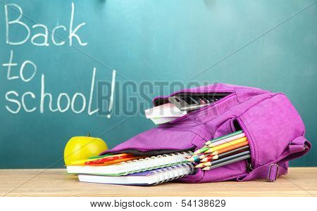 Purple backpack with school supplies on wooden table on green desk background