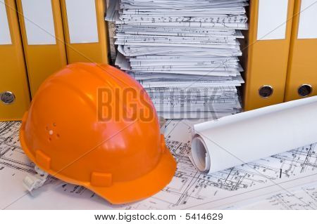 Orange Helmet And Heap Of Project Drawings