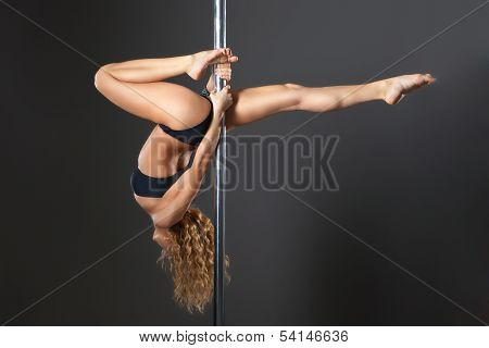 Attractive sexy woman pole dancer performing