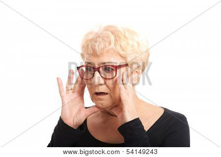 An old lady expresses shock/ surprise. Isolated on white.