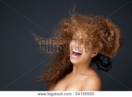 Portrait Of A Happy Young Woman Laughing With Hair Blowing
