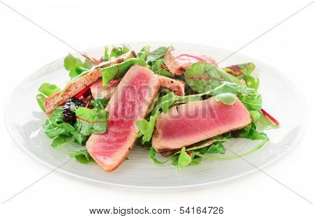 Appetizer with rare fried tuna in plate isolated on white background