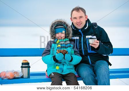 Happy father and son picnicking on winter beach