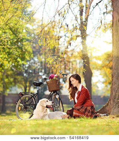 Pretty female sitting down with her labrador retriever dog in a park, shot with a tilt and shift lens